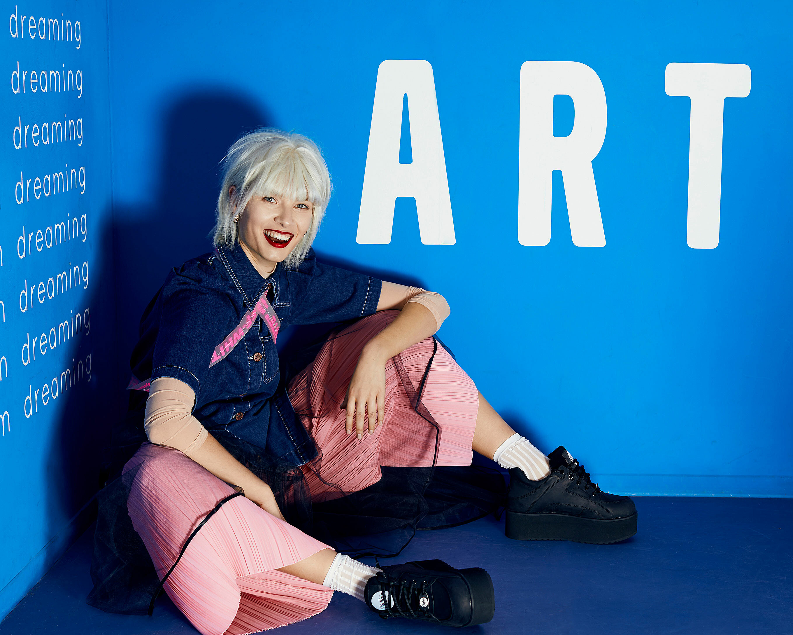 A female model with a blonde wig sits on the floor in a blue corner in pink trousers. She wears also a denim shirt and black buffalos with white socks. She is laughing in front of the camera