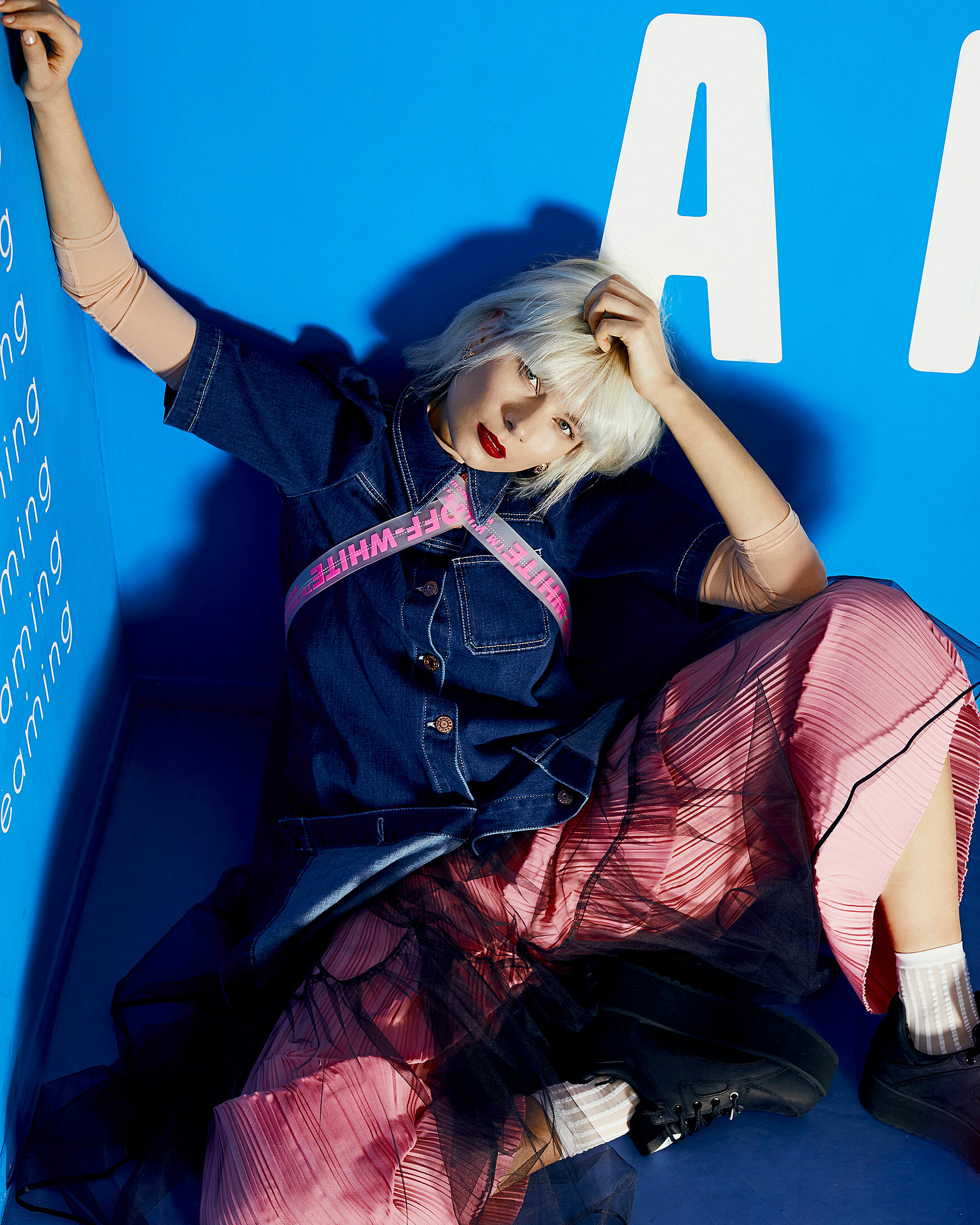 A female model with a blonde wig sits on the floor in a blue corner in pink trousers. She wears also a denim shirt and black buffalos with white socks. She lies relaxed in the corner with her back