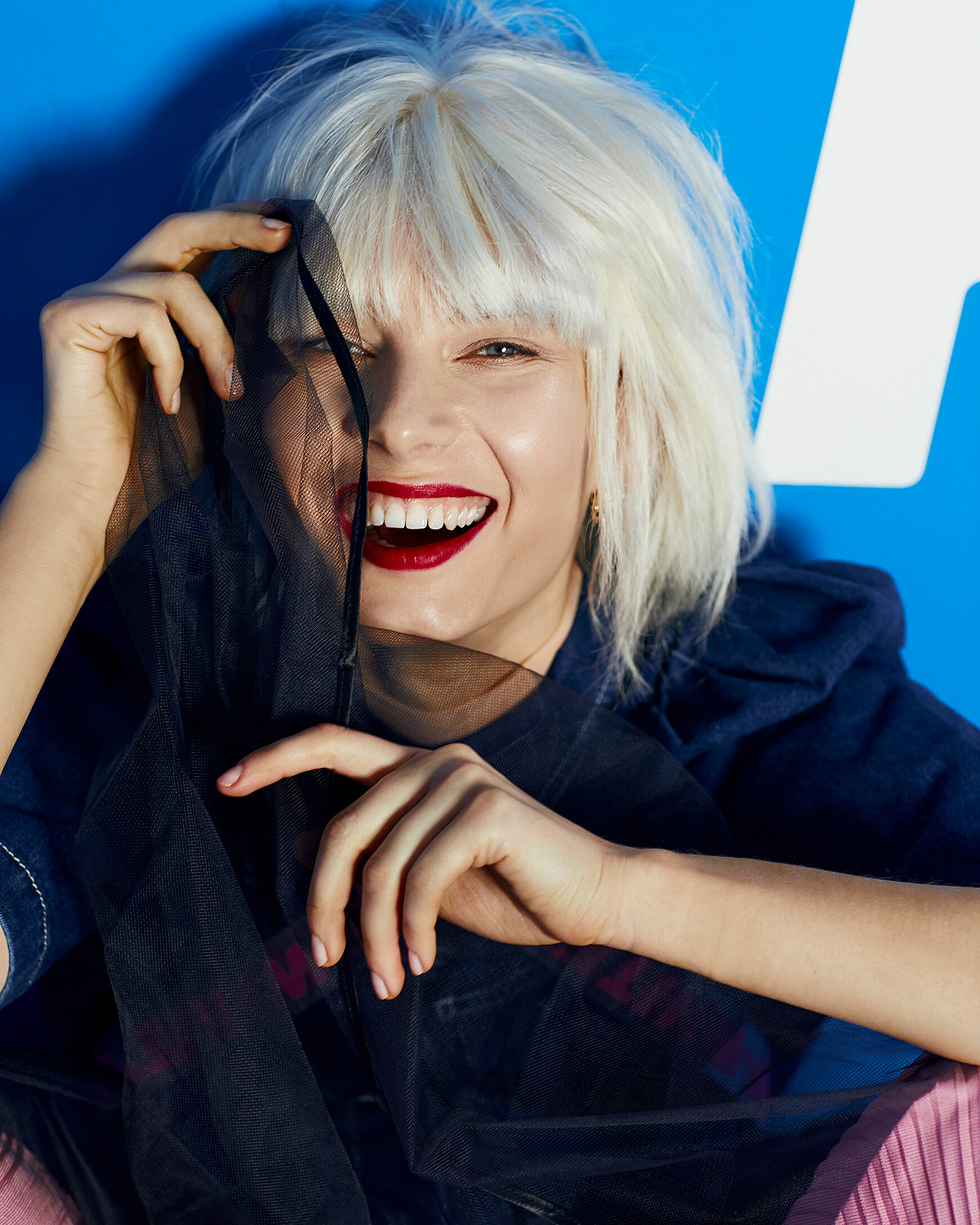 A close up of a female model with a blonde wig. She laughs direct in the camera and hold black semi-tranparency cloth in her hand
