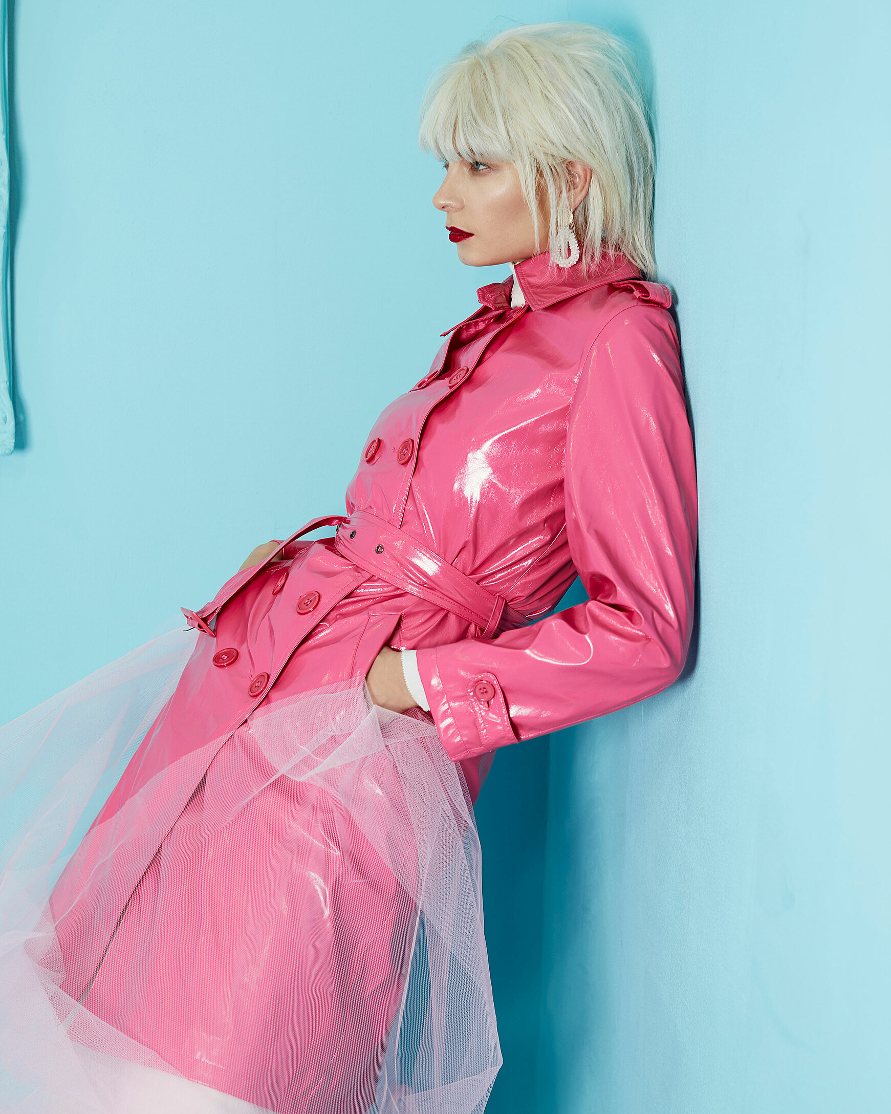 A female model with a blonde wig stands cool on the wall with a pink trench coat and rosy tulle. She wears white earrings and dark red lips