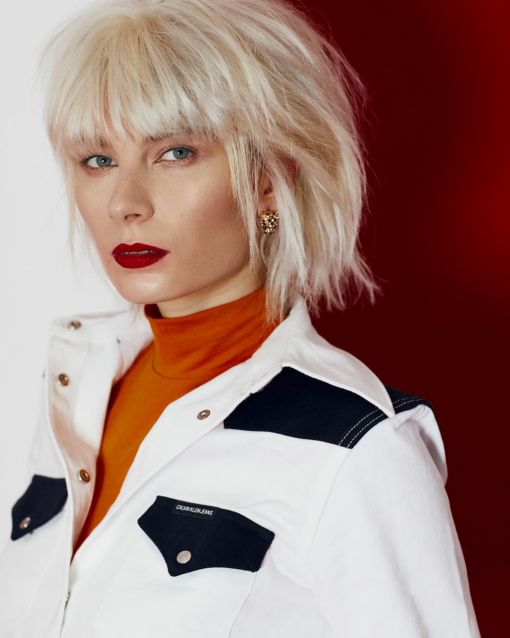 A close up of a female model with a blonde wig in denim white shirt and an orange pullover under it.