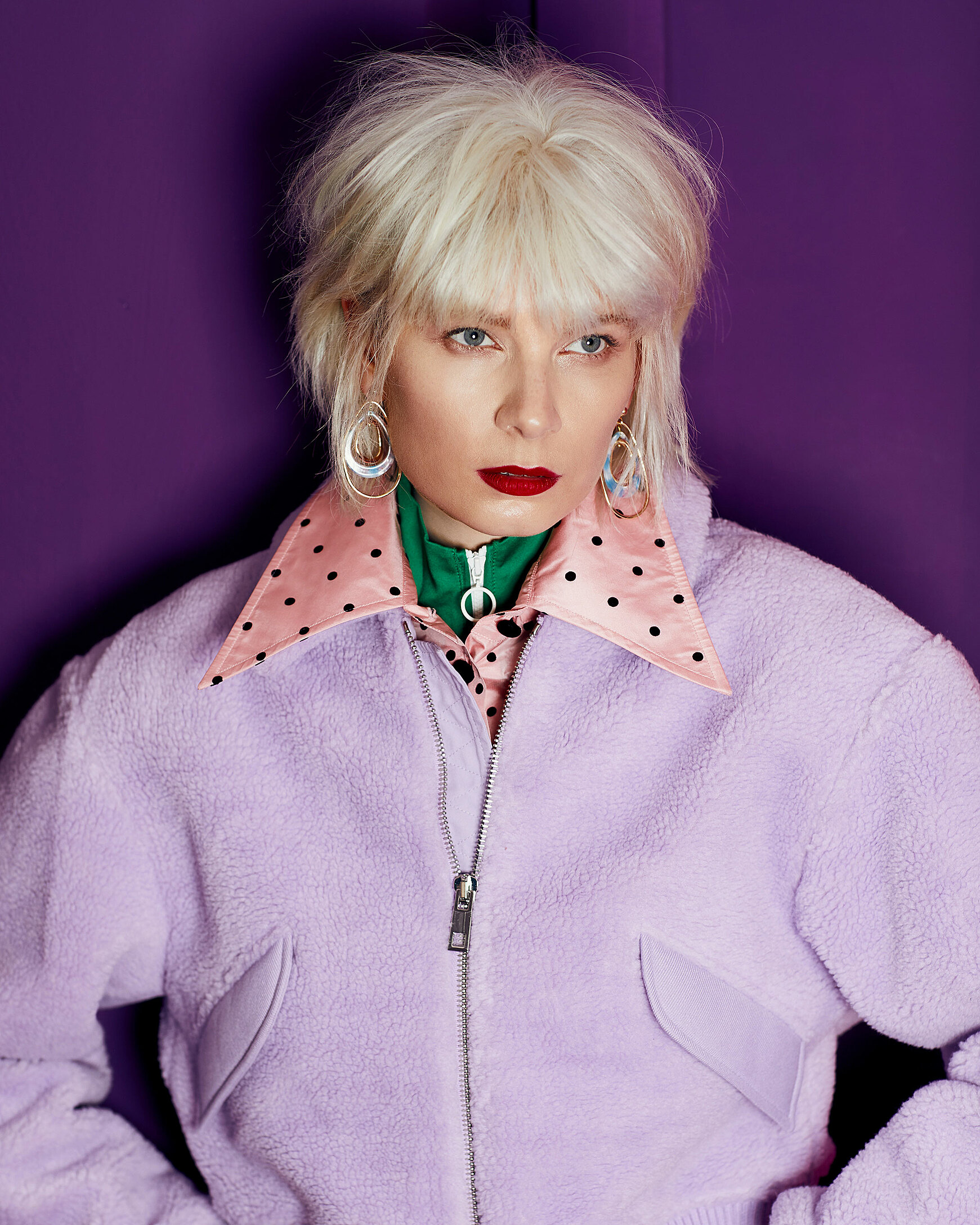 A portrait of a female model with a blonde wig in a light violet cozy jacket and a rose dotted collar
