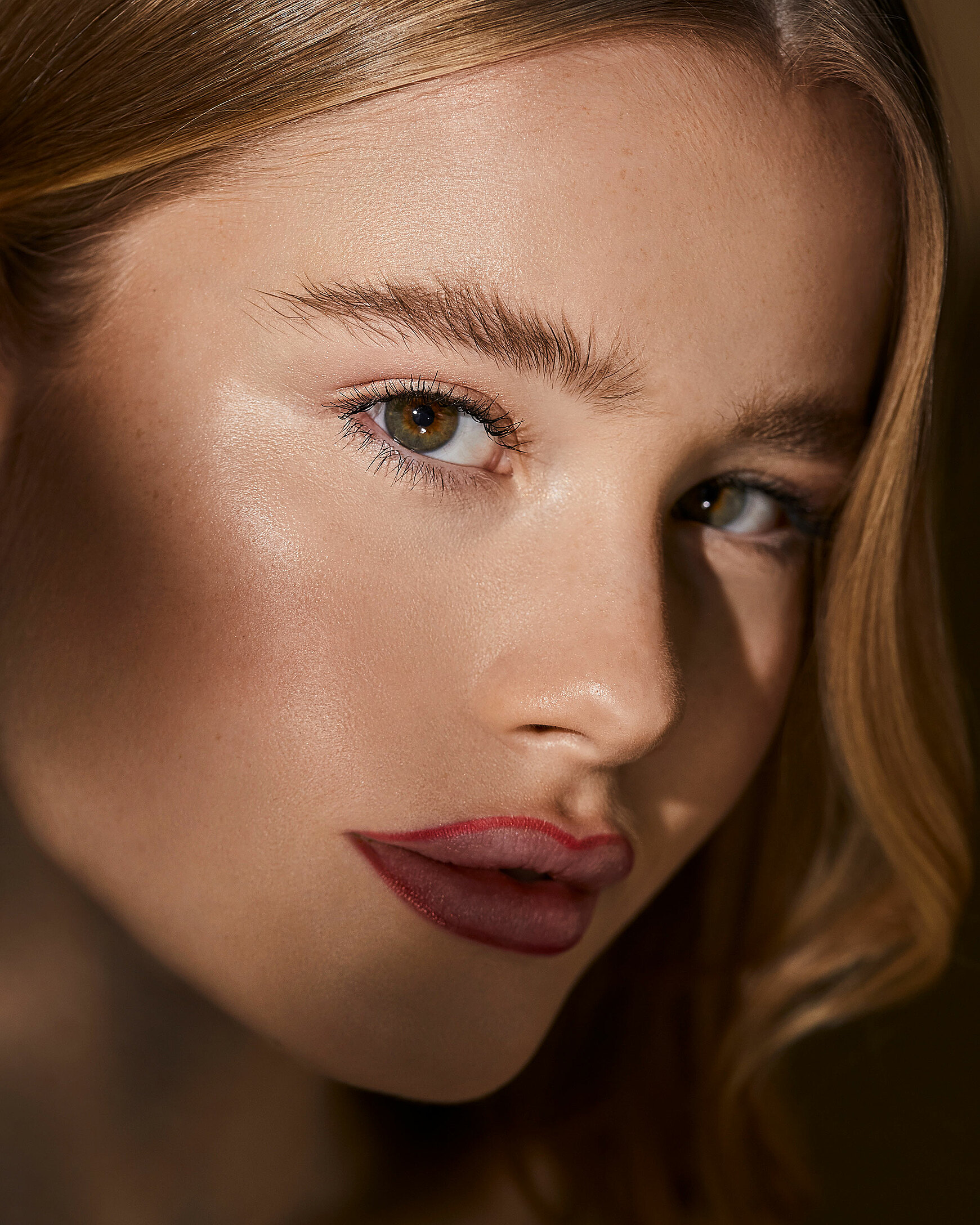 A close-up of a blonde female model. She wears red lipliner around her lips.