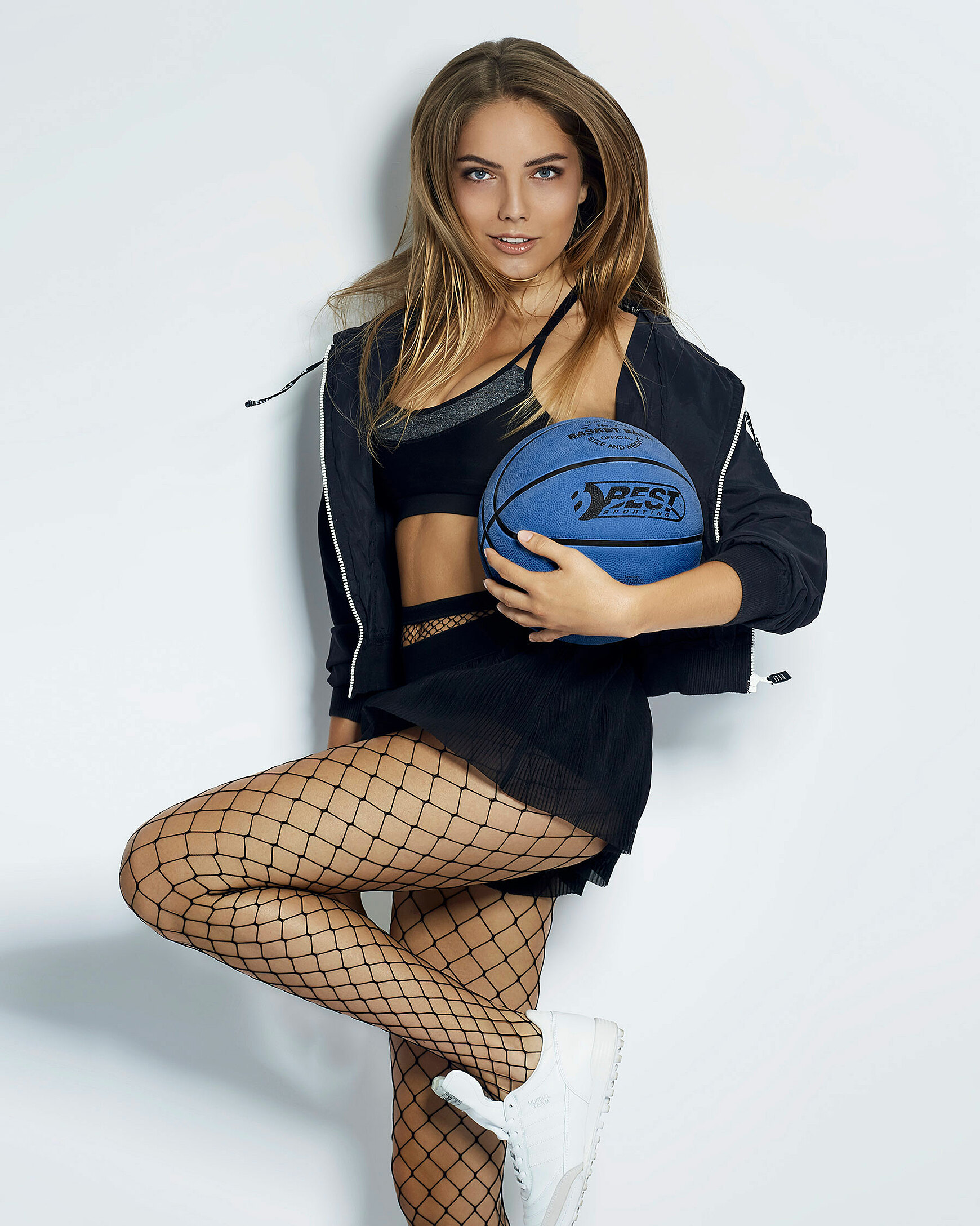 A young model in a sporty outfit with a blue basketball jumped in front of a white wall.
