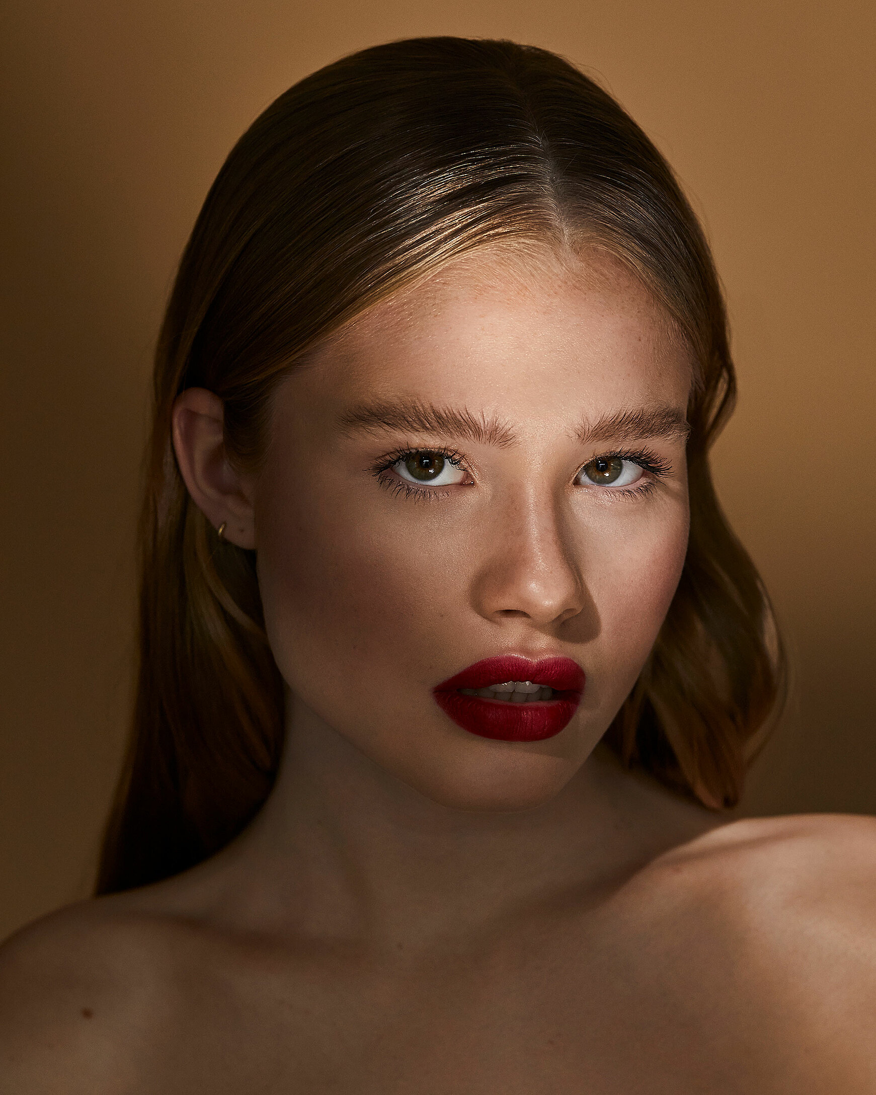 A female blonde model with red lips in a strong pose with sleek hairs