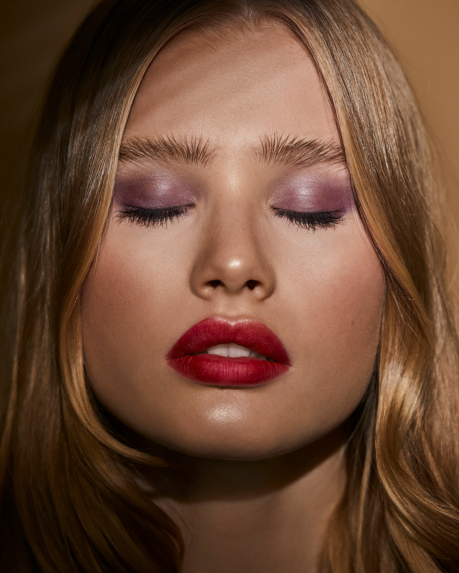 A close-up of a blonde female model closed her eyes. A colorful makeup with red lips and purple eye shadow