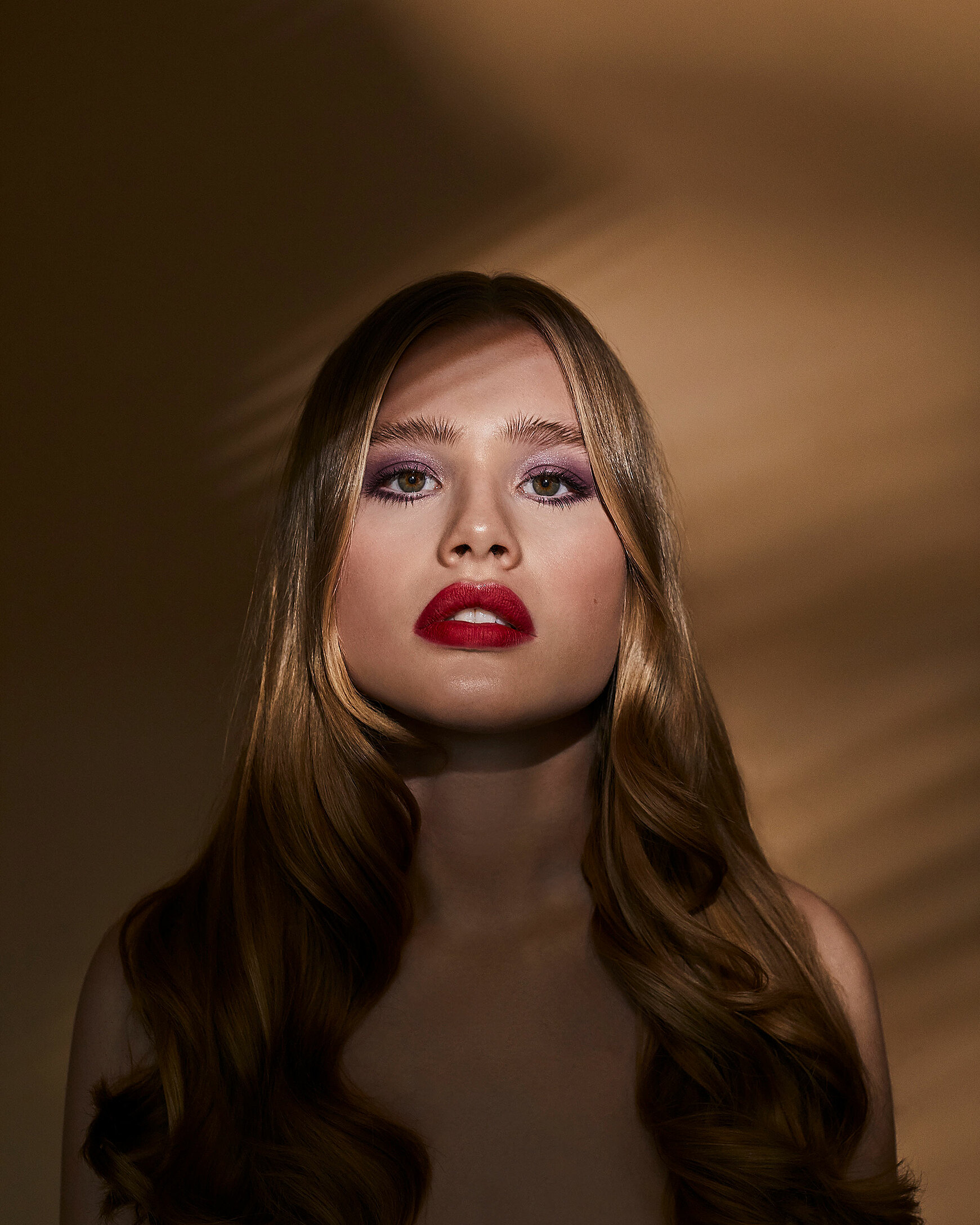 A female blonde model with red lips and purple eye shadow stand straight in front of the camera. The shadow is around her face