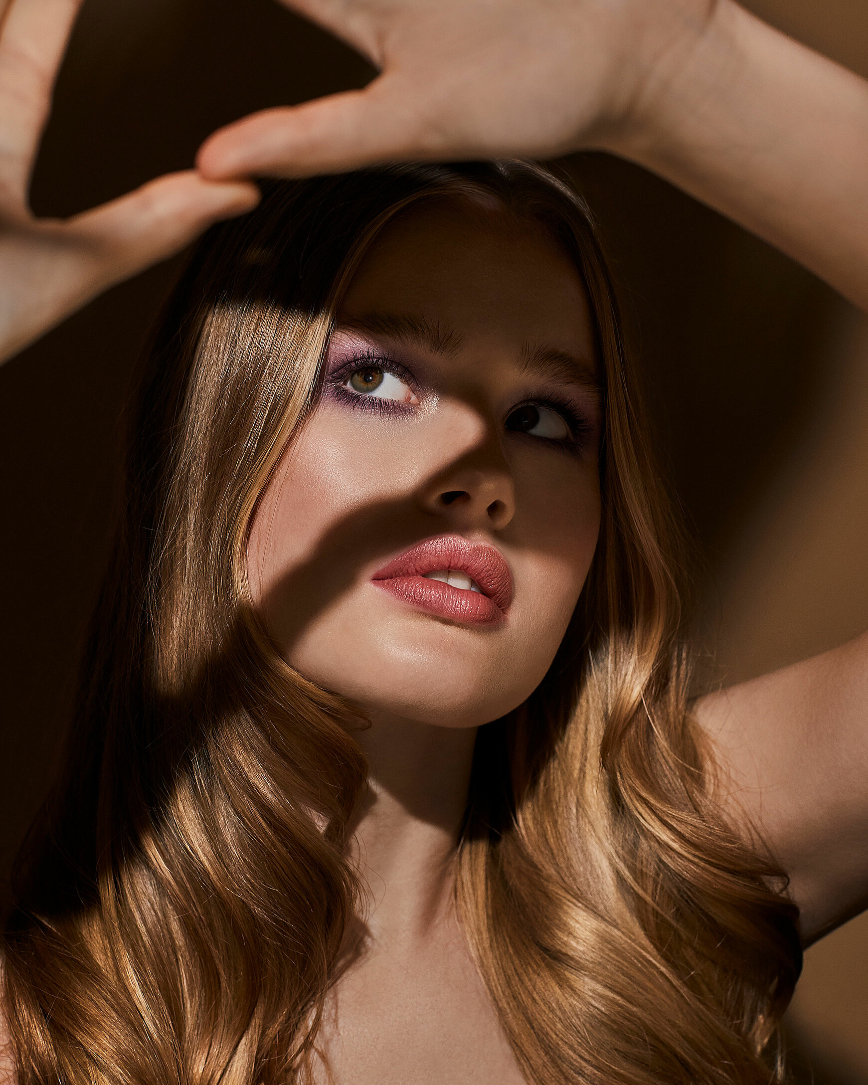 A female blonde model who holds up her hand in shape of a triangle. Her eyes are looking through them. She wears a light red on her lips and purple eye shadow